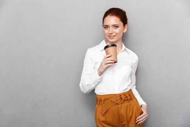 Portret szczęśliwej rudej bizneswoman 20s w formalnym stroju uśmiecha się w biurze i pije kawę na wynos z plastikowego kubka odizolowanego na szaro