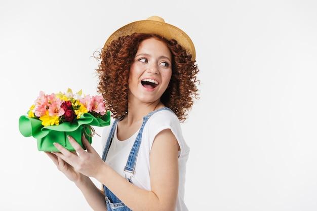 Portret szczęśliwej rudej kręconej kobiety 20 lat w letnim słomkowym kapeluszu uśmiecha się i trzyma pudełko na kwiaty odizolowane nad białą ścianą