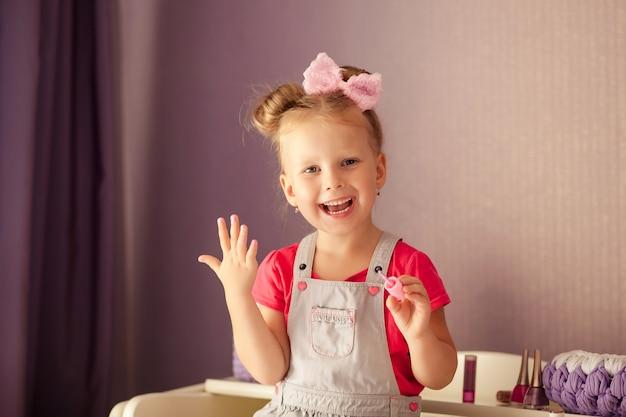 Portret szczęśliwej ślicznej dziewczyny w wieku 3-4 lat, dziecko maluje paznokcie
