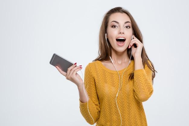 Portret szczęśliwej słodkiej kobiety słuchającej muzyki w słuchawkach na białym tle