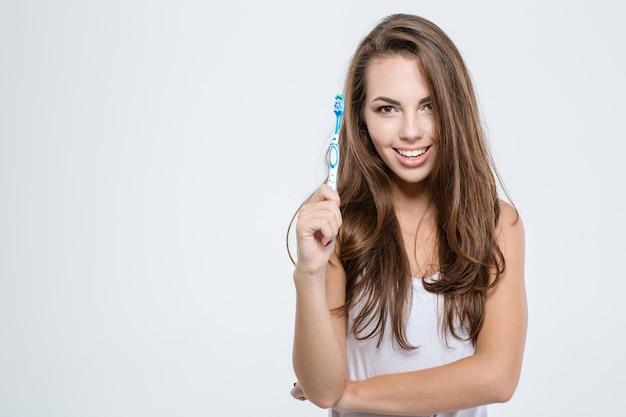 Portret szczęśliwej słodkiej kobiety trzymającej szczoteczkę do zębów na białym tle i patrzącej na kamerę