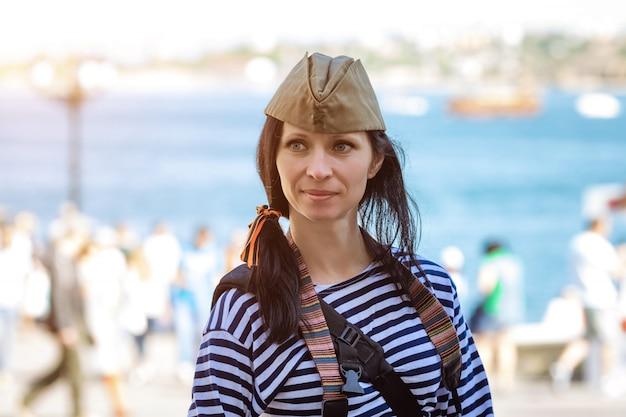 Portret szczęśliwej słodkiej kobiety w kamizelce i czapce wojskowej na głowie