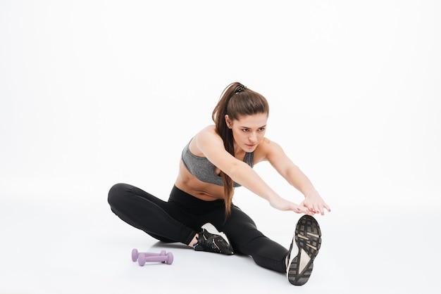 Portret szczęśliwej sportowej kobiety rozciągającej nogi na podłodze na białym tle