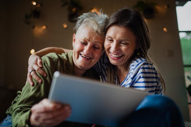 Portret szczęśliwej starszej matki z dorosłą córką w domu w domu, za pomocą tabletu.
