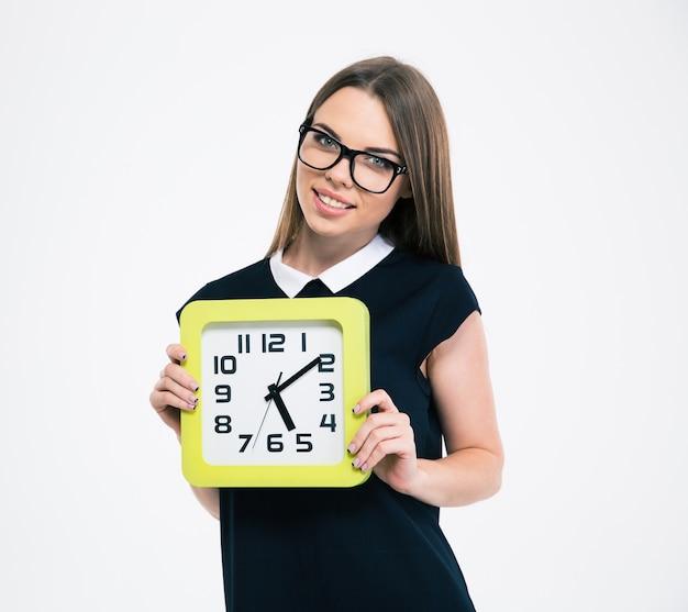 Portret szczęśliwej studentki trzymającej zegar ścienny na białym tle