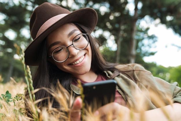 Portret szczęśliwej stylowej kobiety o długich ciemnych włosach, w kapeluszu i okularach, korzystającej z telefonu komórkowego, leżąc na trawie w zielonym parku