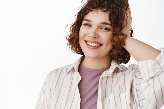 Portret szczęśliwej, szczerej dziewczyny ze zrelaksowaną pozą, wesołym białym uśmiechem i stylową, kręconą krótką fryzurą, dotykającą włosów i patrzącą wesoło na kamerę na biało