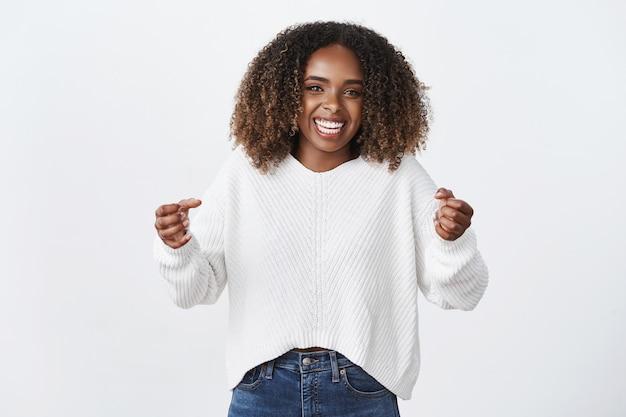 Portret szczęśliwej udanej uroczej i zdumionej ciemnoskórej kobiety wygrywającej nagrody, zaciskając pięści w radości i świętowaniu, triumfując radośnie uśmiechając się nad białą ścianą