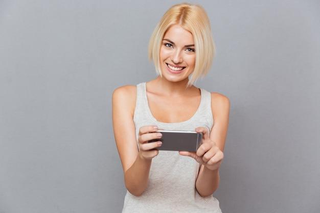 Portret szczęśliwej, uroczej młodej kobiety uśmiechającej się i używającej smartfona na szarej ścianie