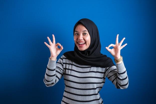 Portret szczęśliwej uśmiechniętej azjatyckiej kobiety muzułmańskiej pokazuje ok gest palca, na niebieskim tle