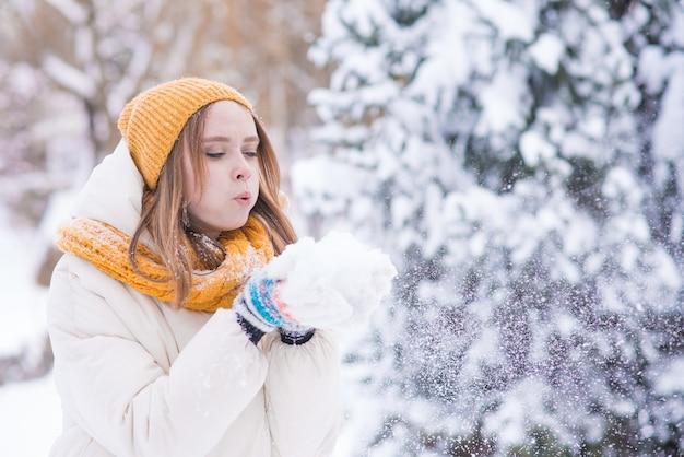 Portret szczęśliwej uśmiechniętej dziewczyny dmuchanie śniegu z rąk w śnieżny zimowy dzień