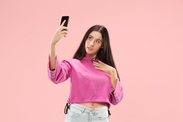 Portret szczęśliwej uśmiechniętej dziewczyny dorywczo pokazującej pusty ekran telefonu komórkowego odizolowanego nad różową ścianą