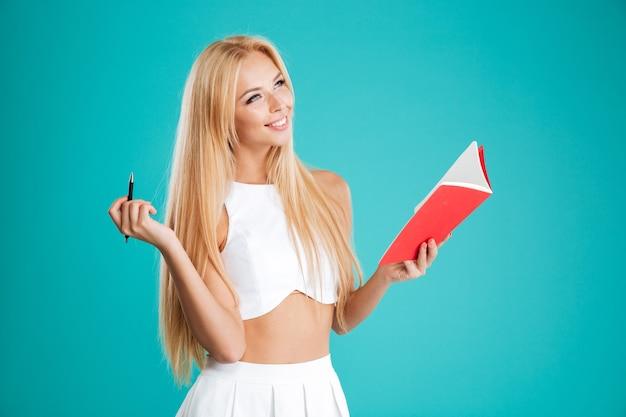 Portret szczęśliwej uśmiechniętej dziewczyny trzymającej notatnik i długopis i odwracającej wzrok na niebieskim tle