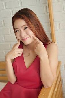 Portret szczęśliwej uśmiechniętej figlarnej azjatyckiej kobiety