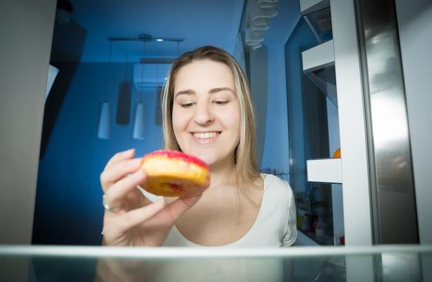 Portret szczęśliwej uśmiechniętej kobiety biorącej pączka z półki lodówki późnym wieczorem