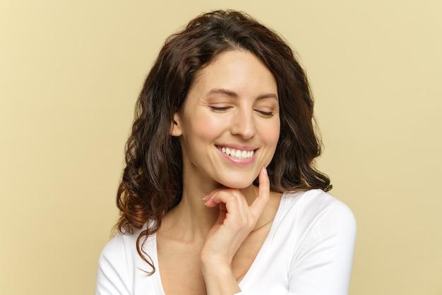 Portret szczęśliwej uśmiechniętej kobiety s dotyk czystej świeżej twarzy po zabiegu kosmetycznym w salonie