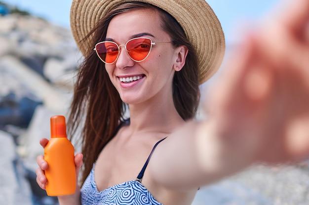Portret szczęśliwej uśmiechniętej kobiety w stroju kąpielowym, słomkowym kapeluszu i jaskrawoczerwonych okularach z butelką kremu do opalania podczas opalania nad morzem w słoneczną pogodę w okresie letnim