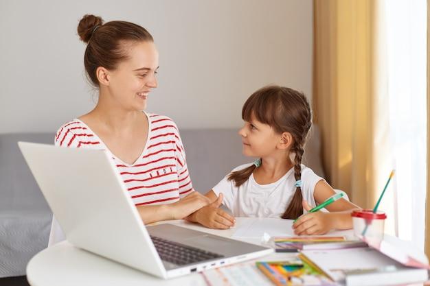 Portret szczęśliwej uśmiechniętej kobiety w swobodnym stroju, pomagającej córce w lekcjach, kobieta patrząca na swoje dziecko z miłością, siedząca przy stole z książkami i laptopem.