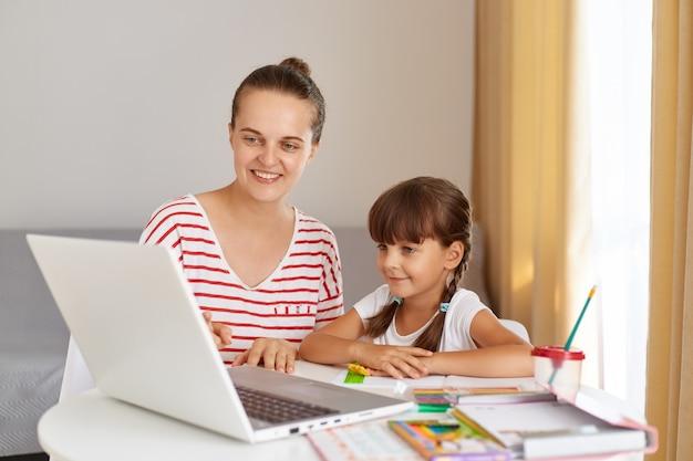 Portret szczęśliwej uśmiechniętej matki siedzącej obok córki małej uczennicy i odrabiającej pracę domową, kobieta pomagająca dziecku z lekcją online, mająca pozytywny wyraz.
