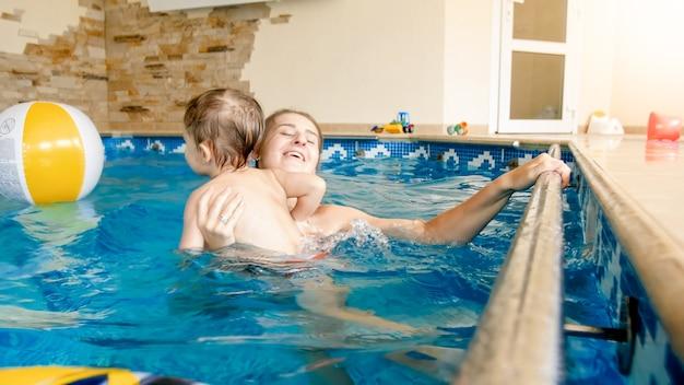Portret szczęśliwej uśmiechniętej matki z 3-letnim synkiem pływającym w basenie na siłowni. rodzinny relaks, zabawy i zabawy w wodzie