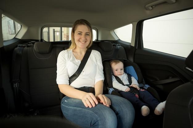Portret szczęśliwej uśmiechniętej matki z dzieckiem na tylnym siedzeniu