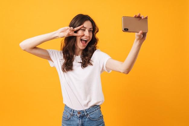 Portret szczęśliwej uśmiechniętej młodej kobiety pozuje na białym tle nad żółtą ścianą, weź selfie telefonem komórkowym, wykonaj gest pokoju