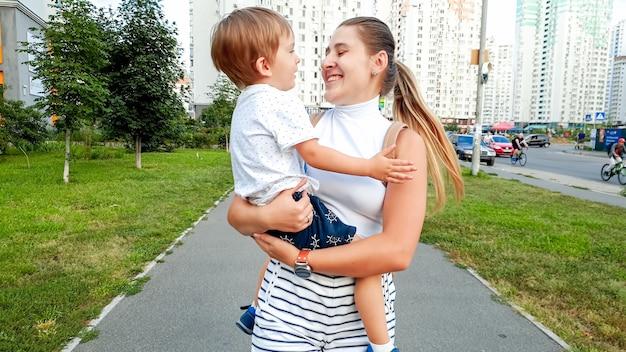 Portret szczęśliwej uśmiechniętej młodej kobiety przytulającej swojego małego syna i idącego ulicą miasta