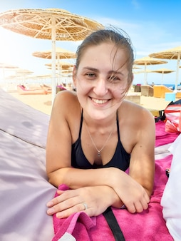 Portret szczęśliwej uśmiechniętej młodej kobiety z długimi włosami, leżącej na leżaku pod parasolem na plaży oceanu i patrzącej w aparacie