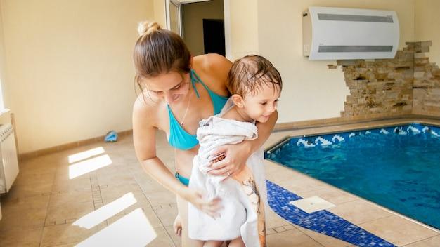 Portret szczęśliwej uśmiechniętej młodej matki wycierającej i rozgrzewającej swojego małego syna dużym białym ręcznikiem po kąpieli w basenie