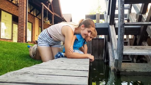 Portret szczęśliwej uśmiechniętej młodej matki z jej małym synkiem dotykającym wody w kanale obok drewnianego młyna wodnego