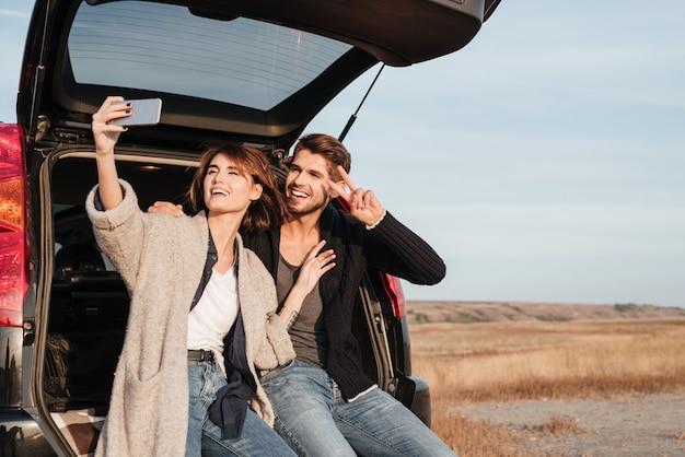 Portret szczęśliwej uśmiechniętej pary biorącej selfie z telefonem komórkowym, siedząc w samochodzie na zewnątrz