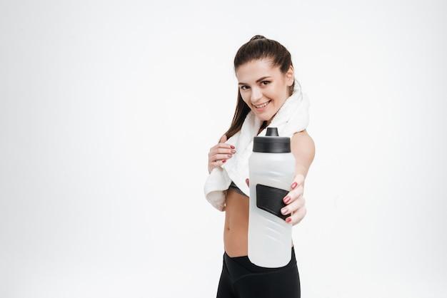 Portret szczęśliwej uśmiechniętej sportowej kobiety podającej butelkę wody do przodu z ręcznikiem na szyi na białym tle