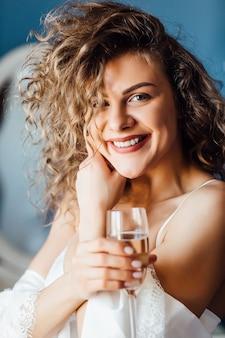 Portret szczęśliwej uśmiechniętej uroczej kobiety z lampką szampana