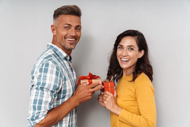 Portret szczęśliwej uśmiechniętej, uroczej, optymistycznej, kochającej się pary dorosłej, odizolowanej nad szarą ścianą, trzymającej dla siebie prezenty