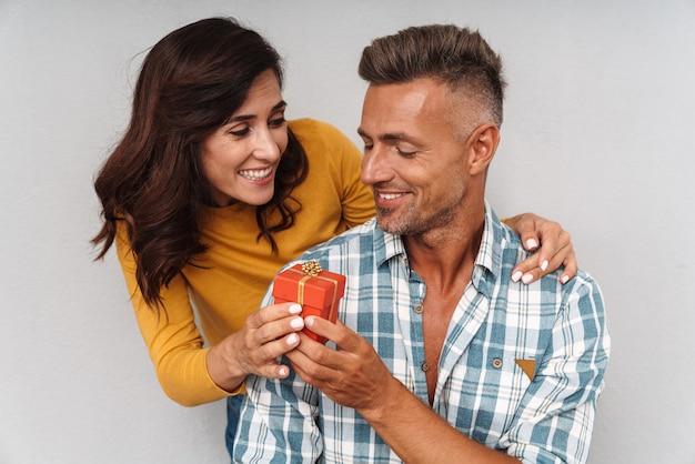 Portret szczęśliwej wesołej kobiety daje prezent swojemu mężczyźnie na białym tle nad szarą ścianą.