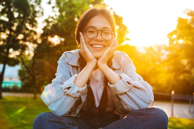 Portret szczęśliwej, wesołej, młodej nastoletniej studentki siedzącej na zewnątrz w pięknym zielonym parku