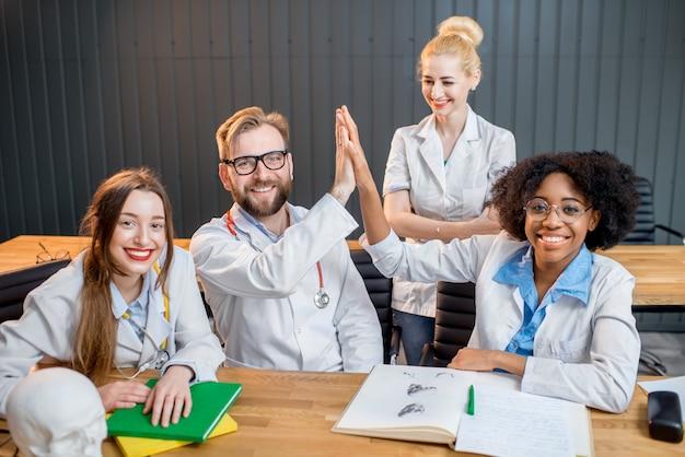 Portret szczęśliwej wieloetnicznej grupy naukowców lub studentów medycyny siedzących razem w biurze lub w klasie