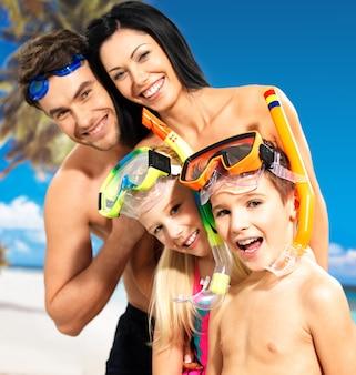 Portret szczęśliwej zabawy pięknej rodziny z dwójką dzieci na tropikalnej plaży z ochronną maską do pływania