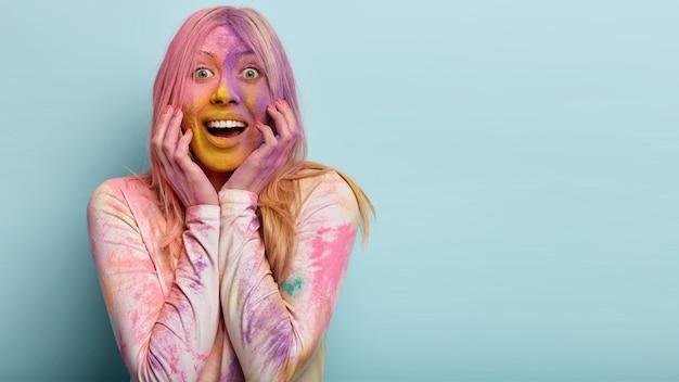 Portret szczęśliwej, zachwyconej kobiety uśmiecha się pozytywnie, pokazuje białe zęby, ma przyjazny wyraz, zadowolona z festiwalu holi colours, pudrowana kolorowym barwnikiem, stoi w pomieszczeniu, puste miejsce na tekst