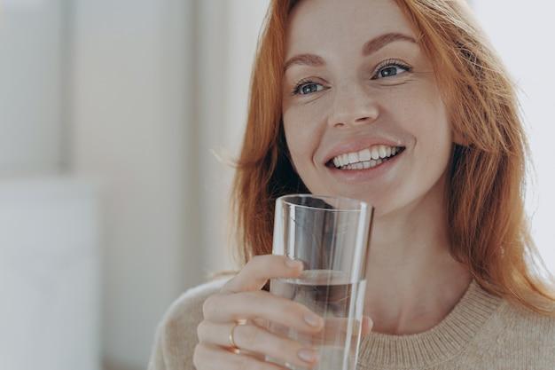Portret szczęśliwej zdrowej kobiety imbirowej trzymającej przezroczystą szklankę czystej wody mineralnej