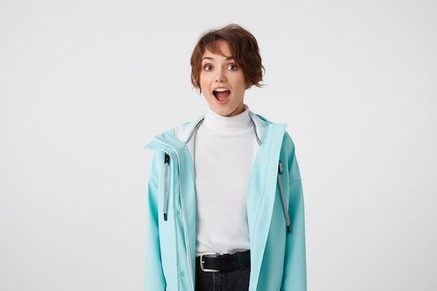 Portret szczęśliwej zdumionej krótkowłosej kędzierzawej pani w białym golfie i jasnoniebieskim płaszczu przeciwdeszczowym, stoi na białym tle z szeroko otwartymi ustami i zaskoczonym wyrazem.