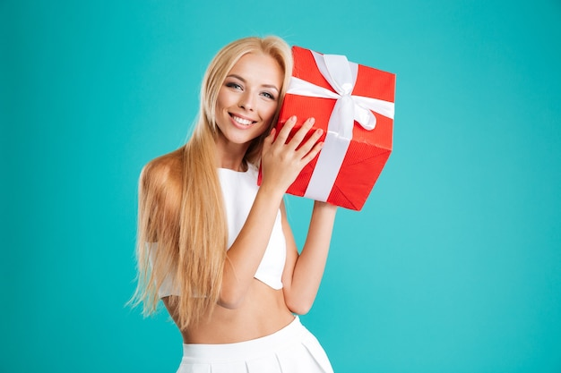 Portret szczęśliwej zdziwionej kobiety trzymającej pudełko na białym tle na niebieskim tle