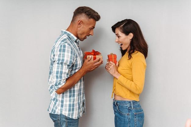 Portret szczęśliwej, zdziwionej, uroczej, optymistycznej, kochającej się pary, odizolowanej nad szarą ścianą, trzymającej dla siebie prezenty