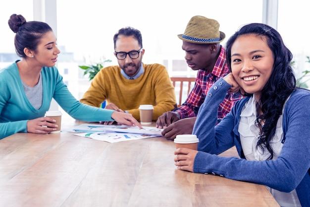 Portret szczęśliwi biznesowej kobiety koledzy dyskutuje przy kreatywnie biurem