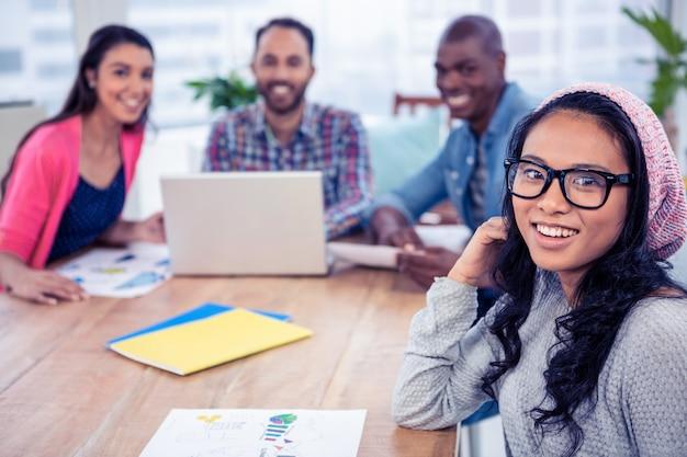 Portret szczęśliwi biznesowi koledzy przy biurkiem w biurze