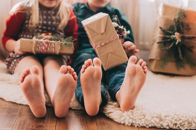 Portret szczęśliwi dzieci z bożenarodzeniowymi dekoracjami. dwoje dzieci, zabawy w domu