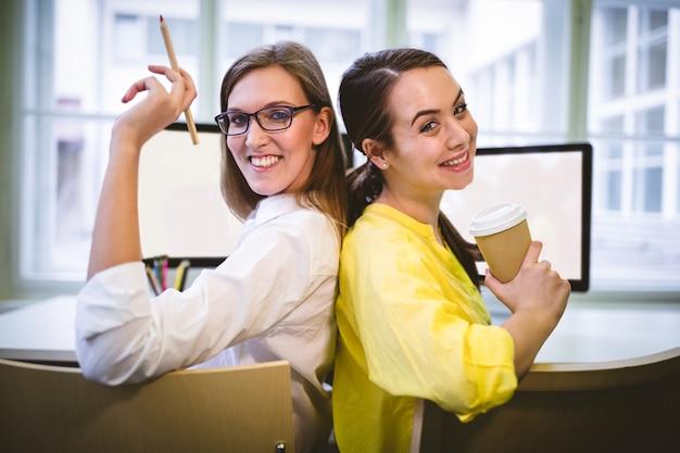 Portret szczęśliwi koledzy siedzi z powrotem popierać przy biurem