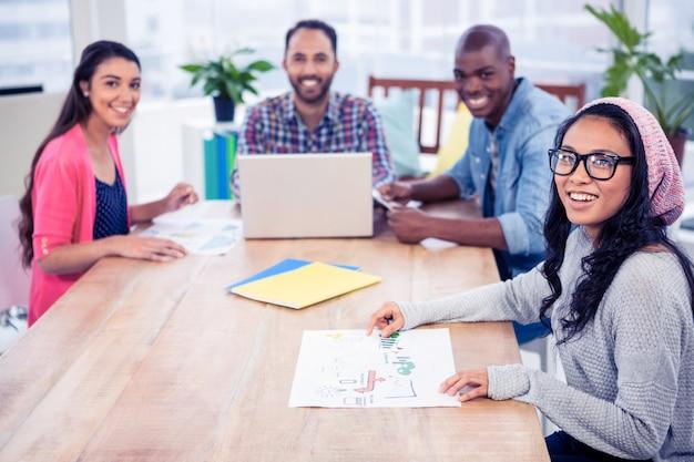 Portret szczęśliwi ludzie biznesu przy biurkiem w biurze
