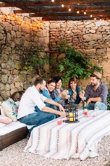 Portret szczęśliwi młodzi ludzie siedzi wpólnie i śmia się podczas gdy cieszący się przy przyjęciem z winem na stole.