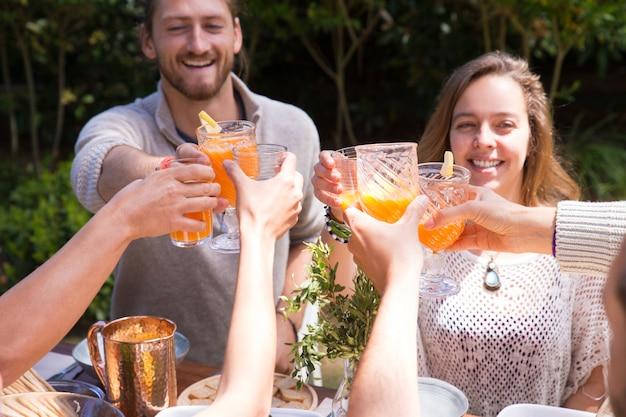 Portret szczęśliwi młodzi przyjaciele wznosi toast sok outdoors